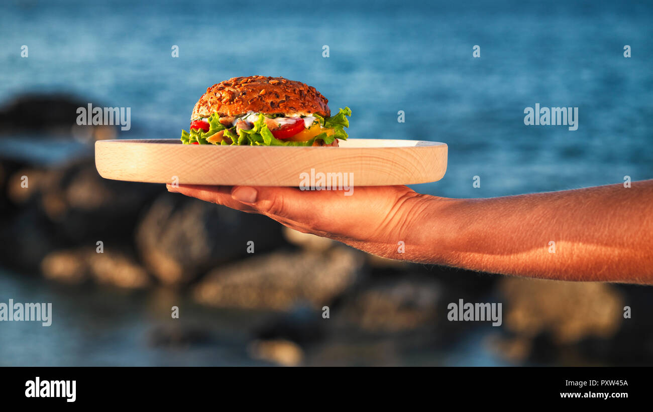 Woman's hand holding wooden plate with fishburger in front of the sea - Stock Image
