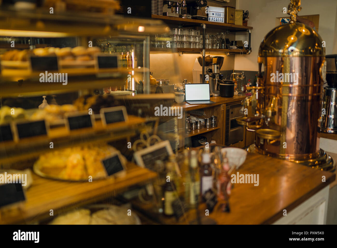 Laptop with blank screen in coffee shop - Stock Image
