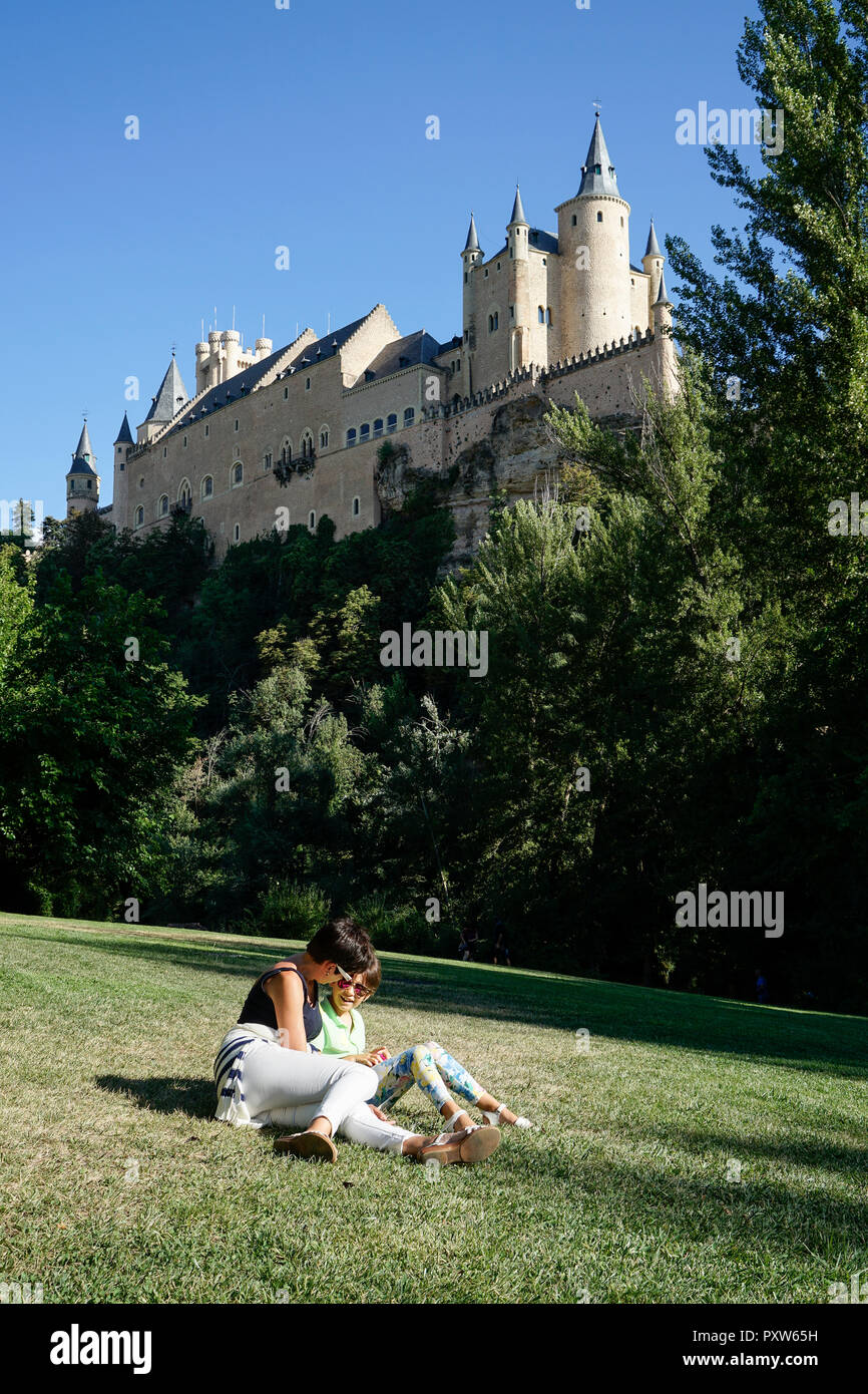 Spain, Castile and Leon, Segovia, Mother and daughter sitting on grass near to Alcazar of Segovia - Stock Image