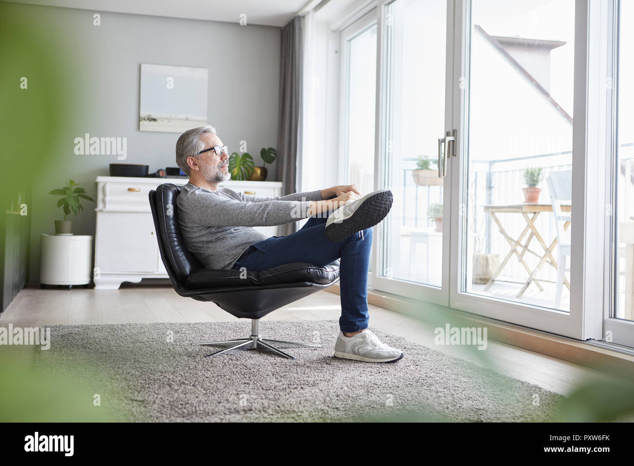 Mature man relaxing on leather chair in his living room looking out of window - Stock Image
