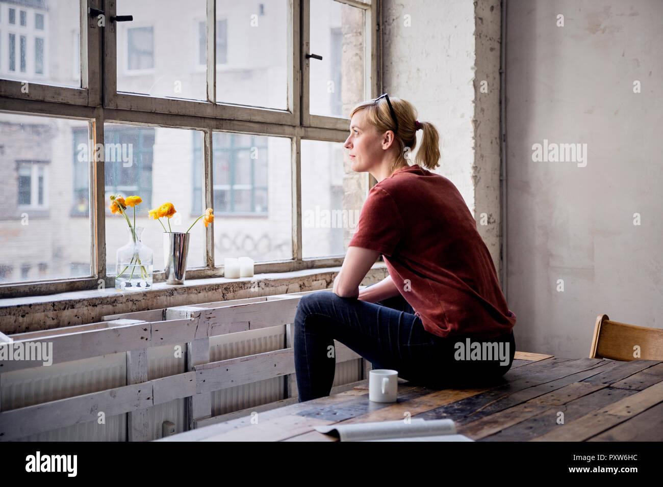 Woman sitting on desk in loft looking through window - Stock Image