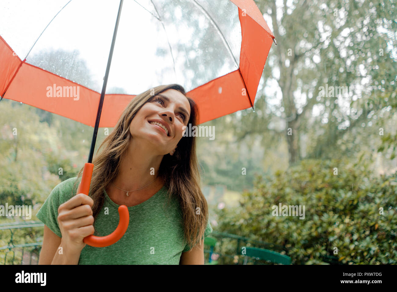 Smiling mature woman standing in rain under umbrella Stock Photo