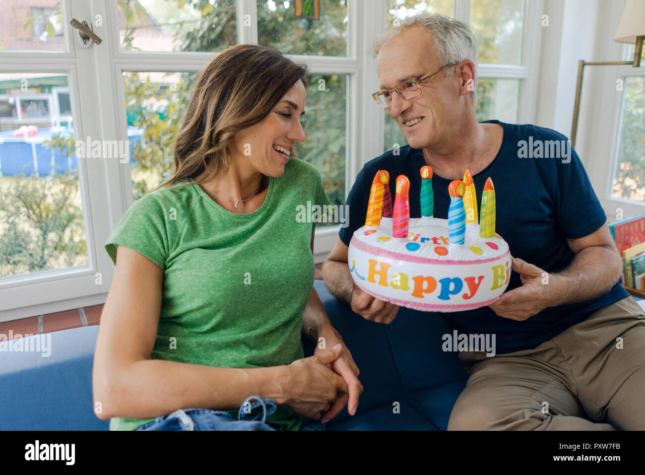 Sensational Happy Mature Couple Sitting On Couch At Home With Fake Birthday Personalised Birthday Cards Fashionlily Jamesorg