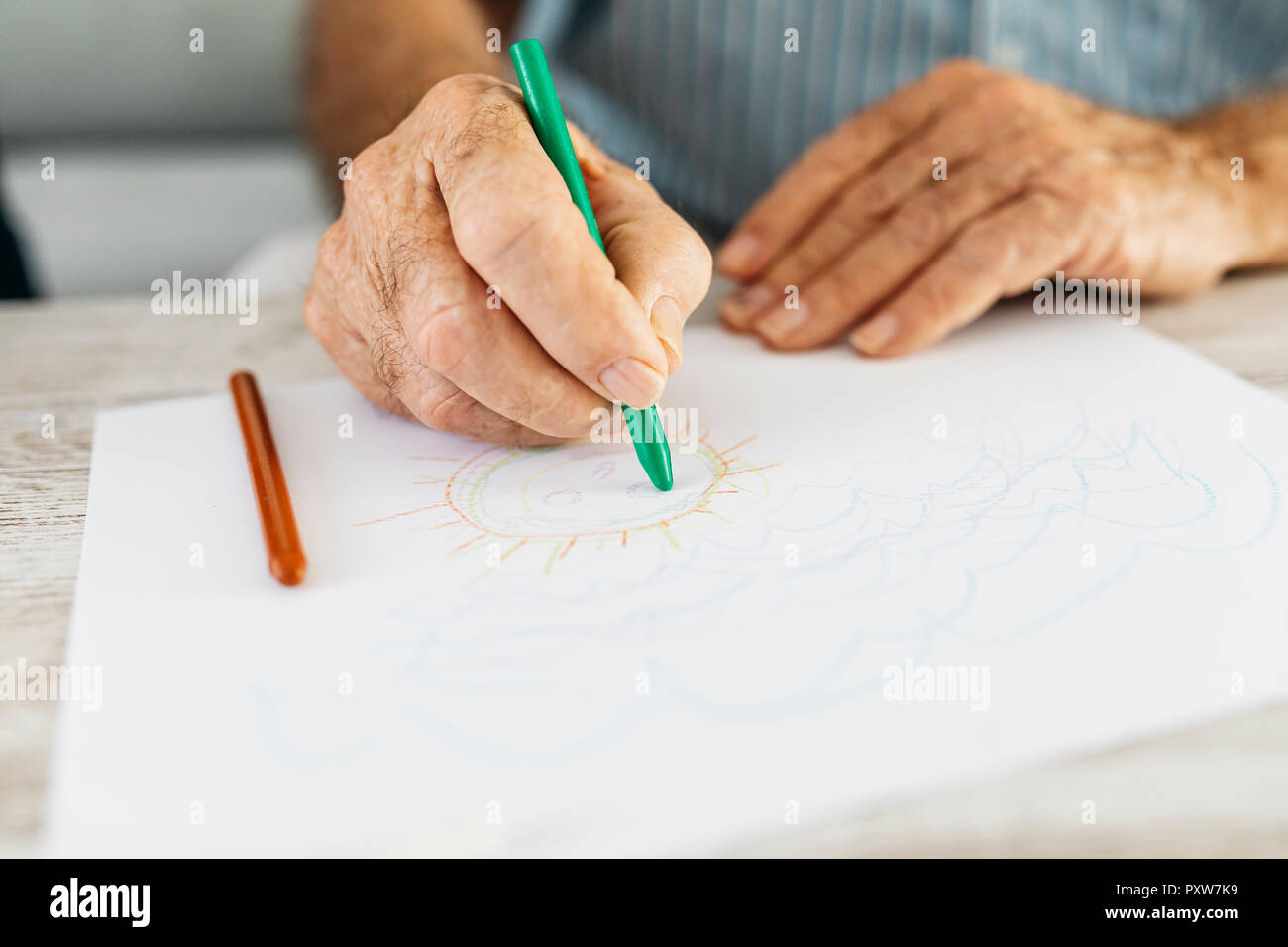 Senior man's hand drawing with green pencil, close-up - Stock Image