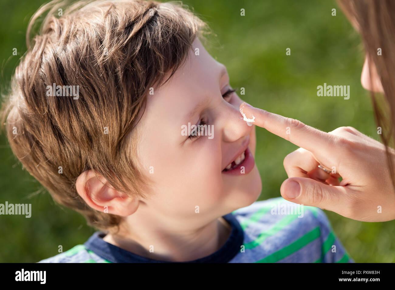Mother applying suncream on son's nose - Stock Image