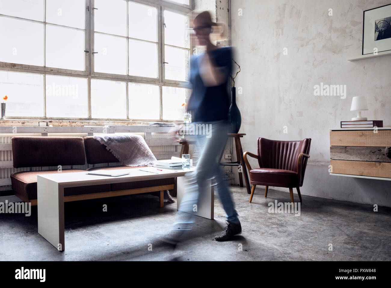 Woman walking in a loft - Stock Image