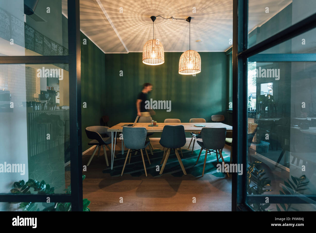 Man walking alone in office of his start up company, working long hours - Stock Image