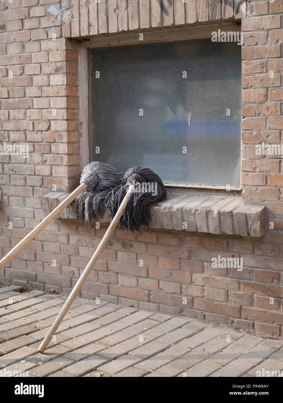 Two cleaning mops leaning on window sill - Stock Image