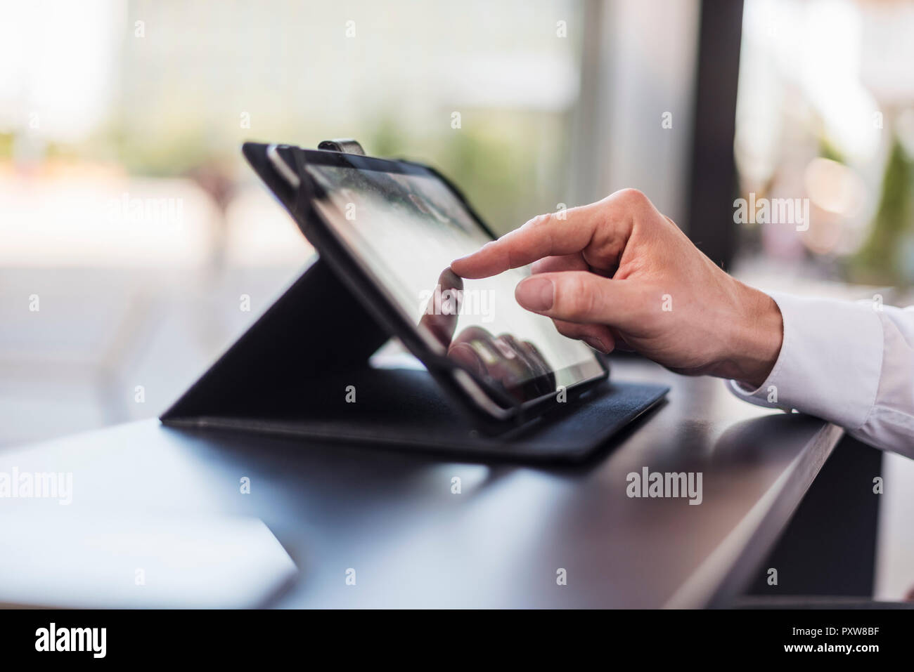 Close-up of businessman using tablet in a cafe - Stock Image