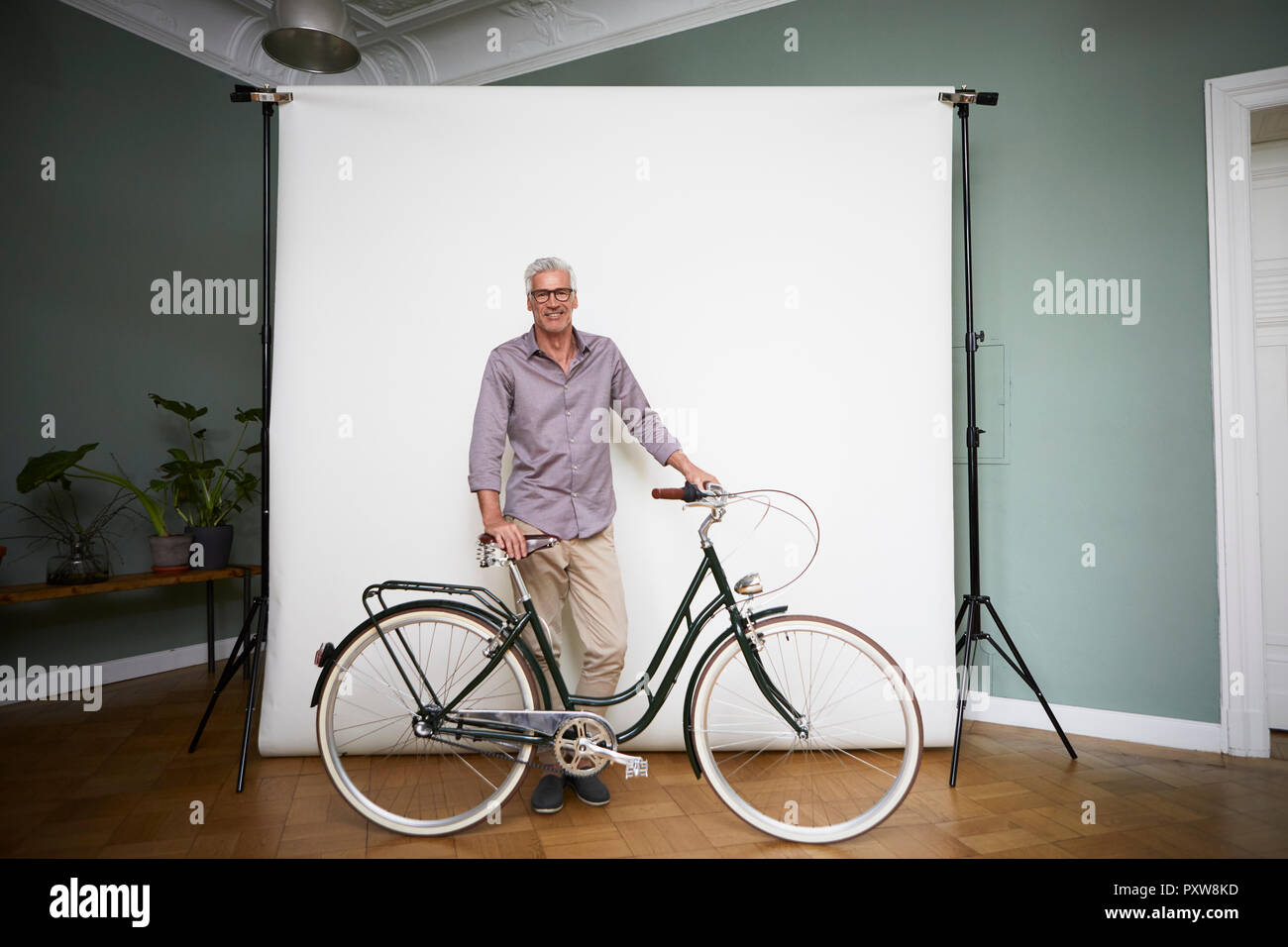 Portait of mature man posing with bicycle at projection screen - Stock Image
