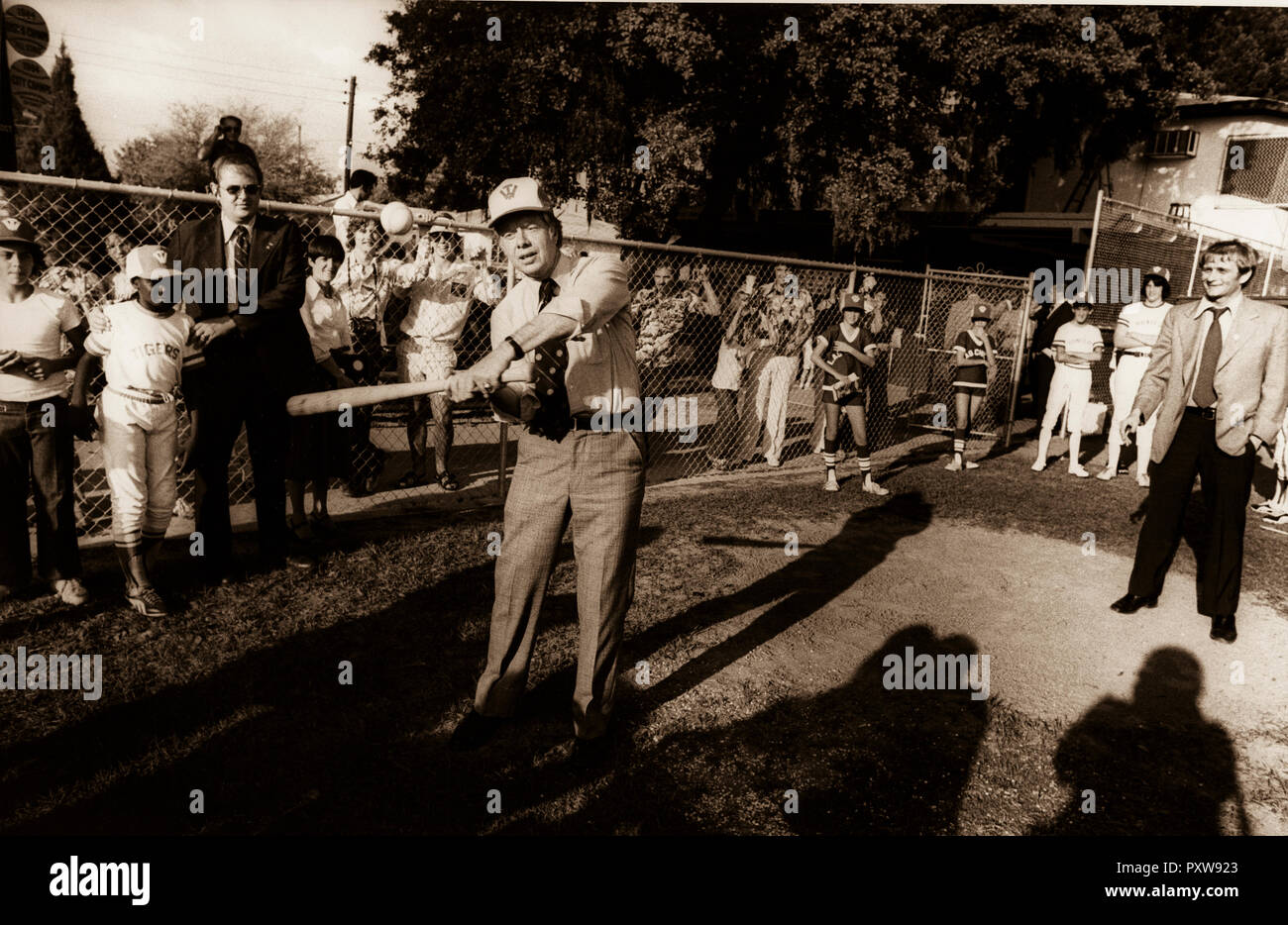 1976 Democratic presidential nominee Jimmy Carter stops his motorcade enroute to a rally in order to visit with elementary school children. Several of the children invited Carter to join them on the baseball field. Carter press secretary, Jody Powell is on far right and a US Secret Service agent holds a boy out of harms way as Carter takes a swing. - Stock Image
