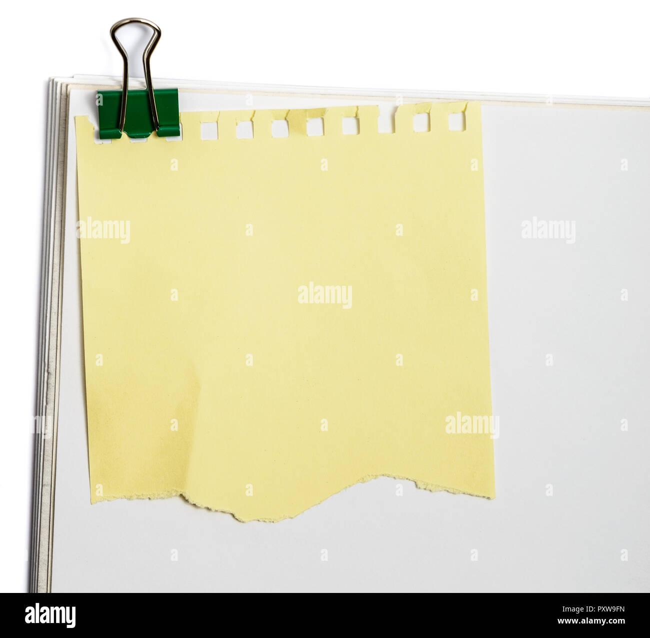 sticker reminder yellow note with clip on white office paper - Stock Image