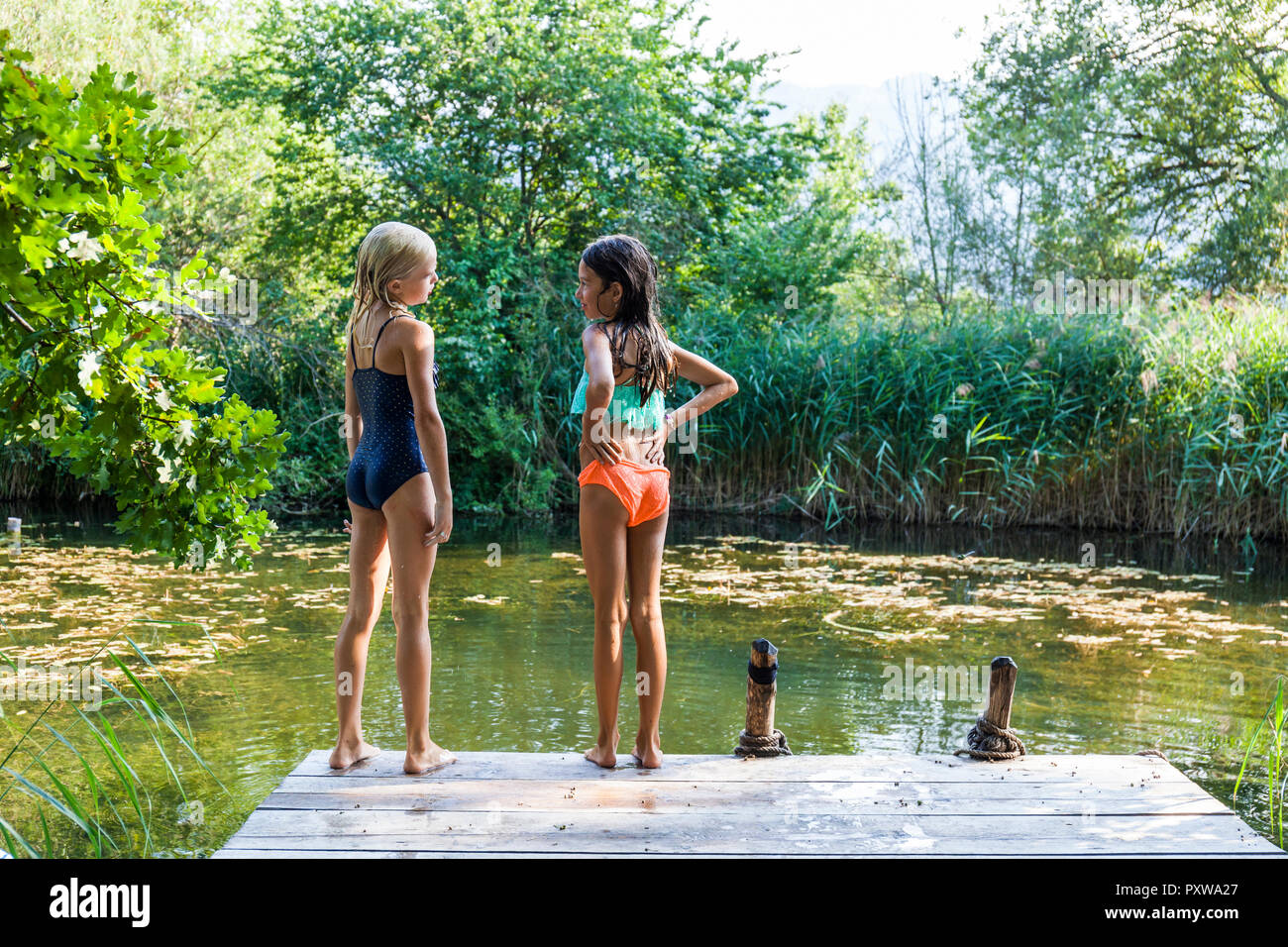 Two girls standing on jetty at a pond talking Stock Photo