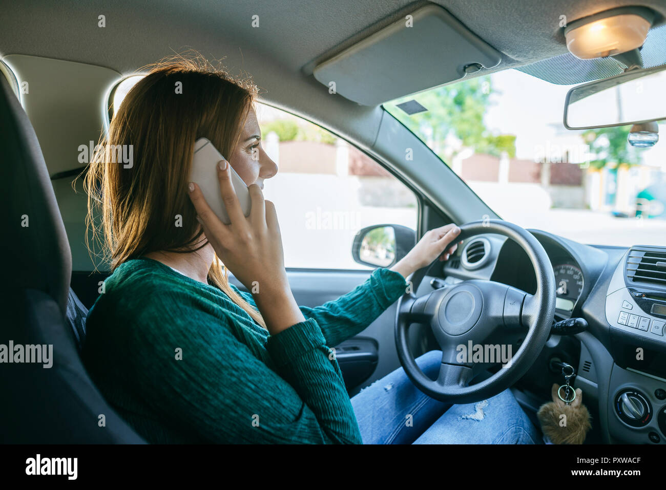 Woman talking on the mobile phone inside of a car - Stock Image