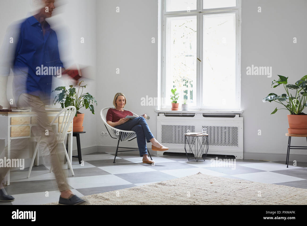 Mature woman reading magazine at home with man passing by - Stock Image