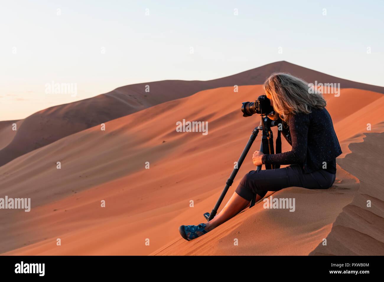 Africa, Namibia, Namib desert, Naukluft National Park, female photograper photographing at early morning light, sitting on sand dune - Stock Image