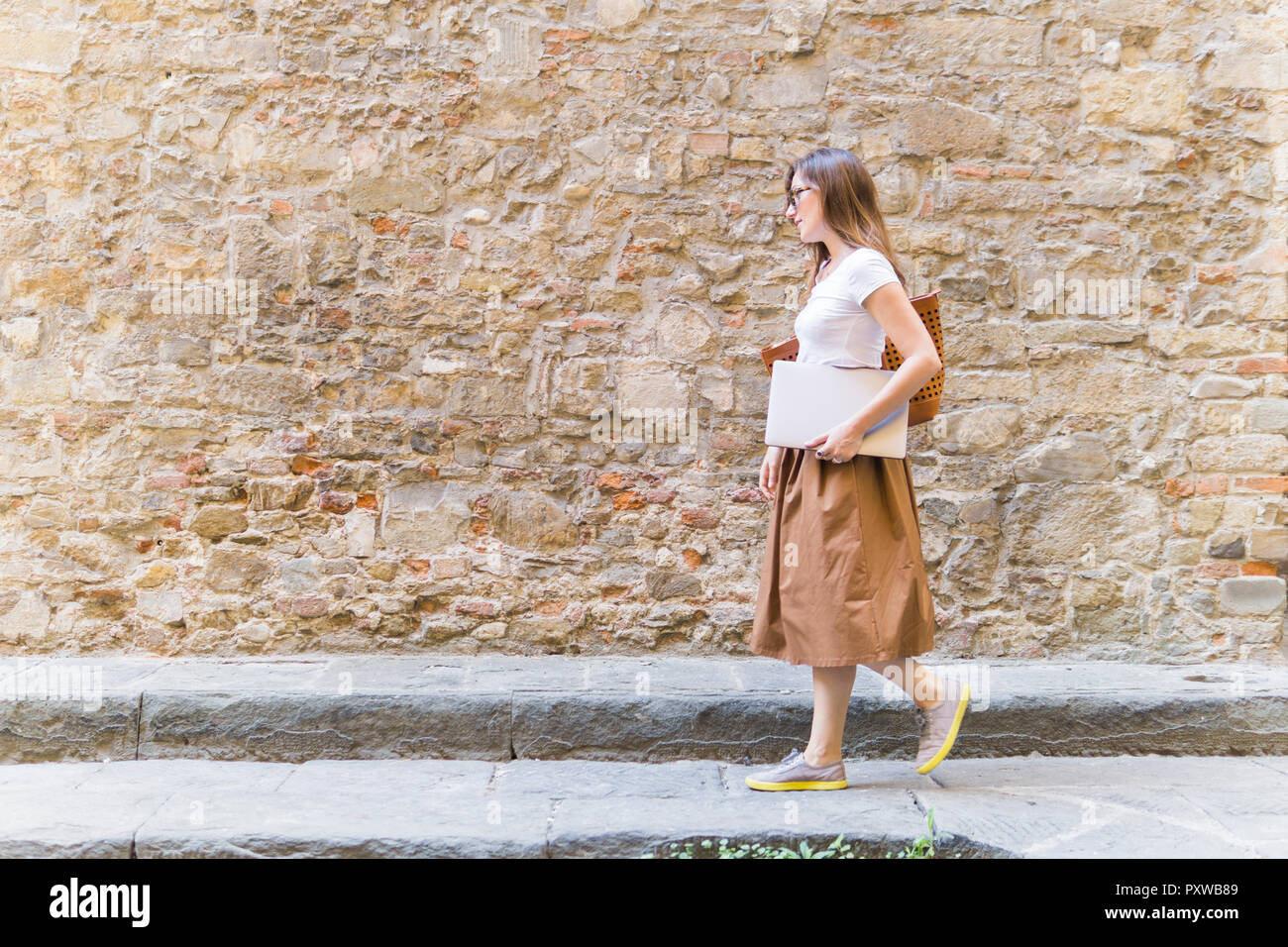 Woman walking along a stone wall carrying laptop - Stock Image
