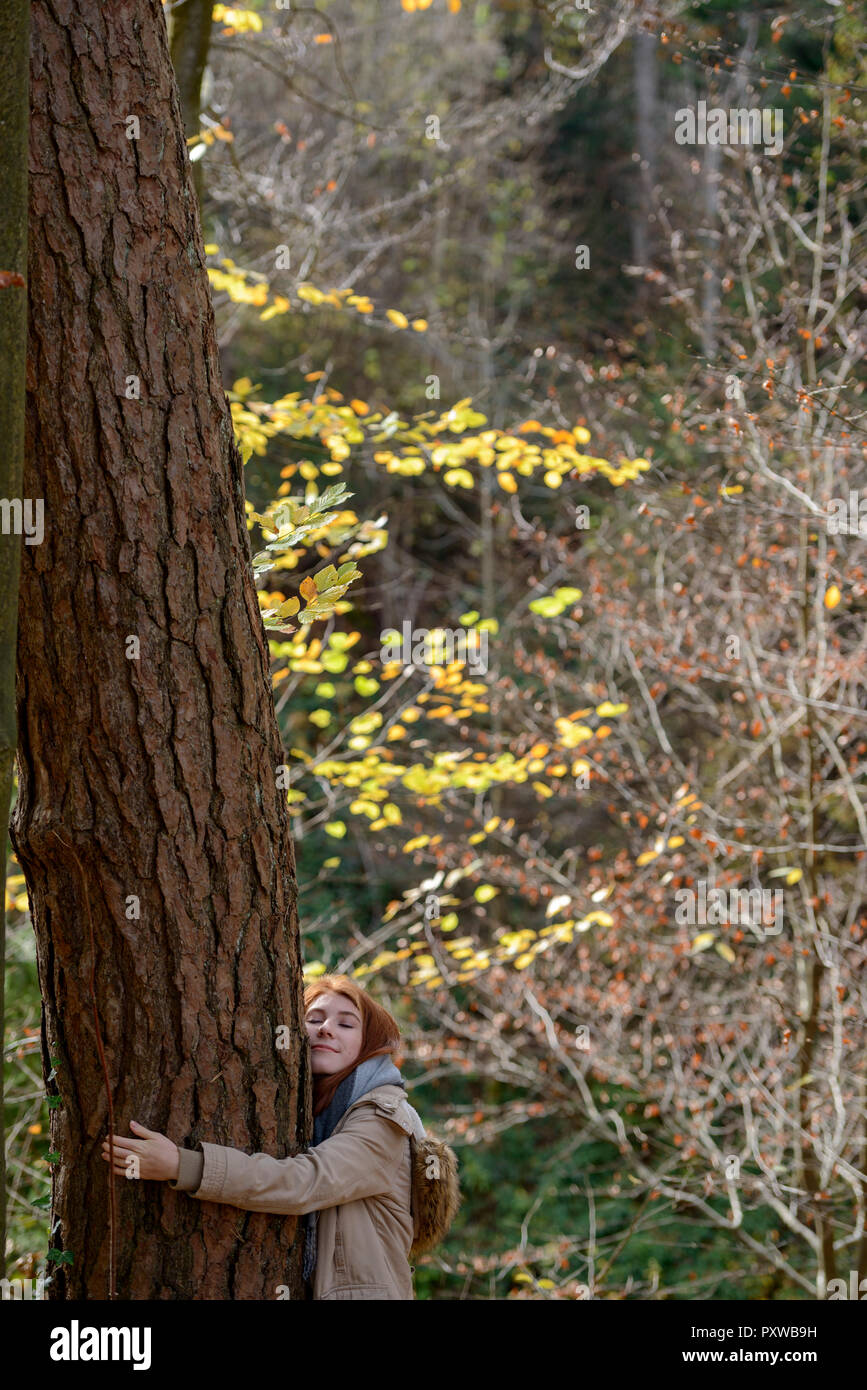 Smiling teenage girl hugging tree trunk in autumnal forest Stock Photo
