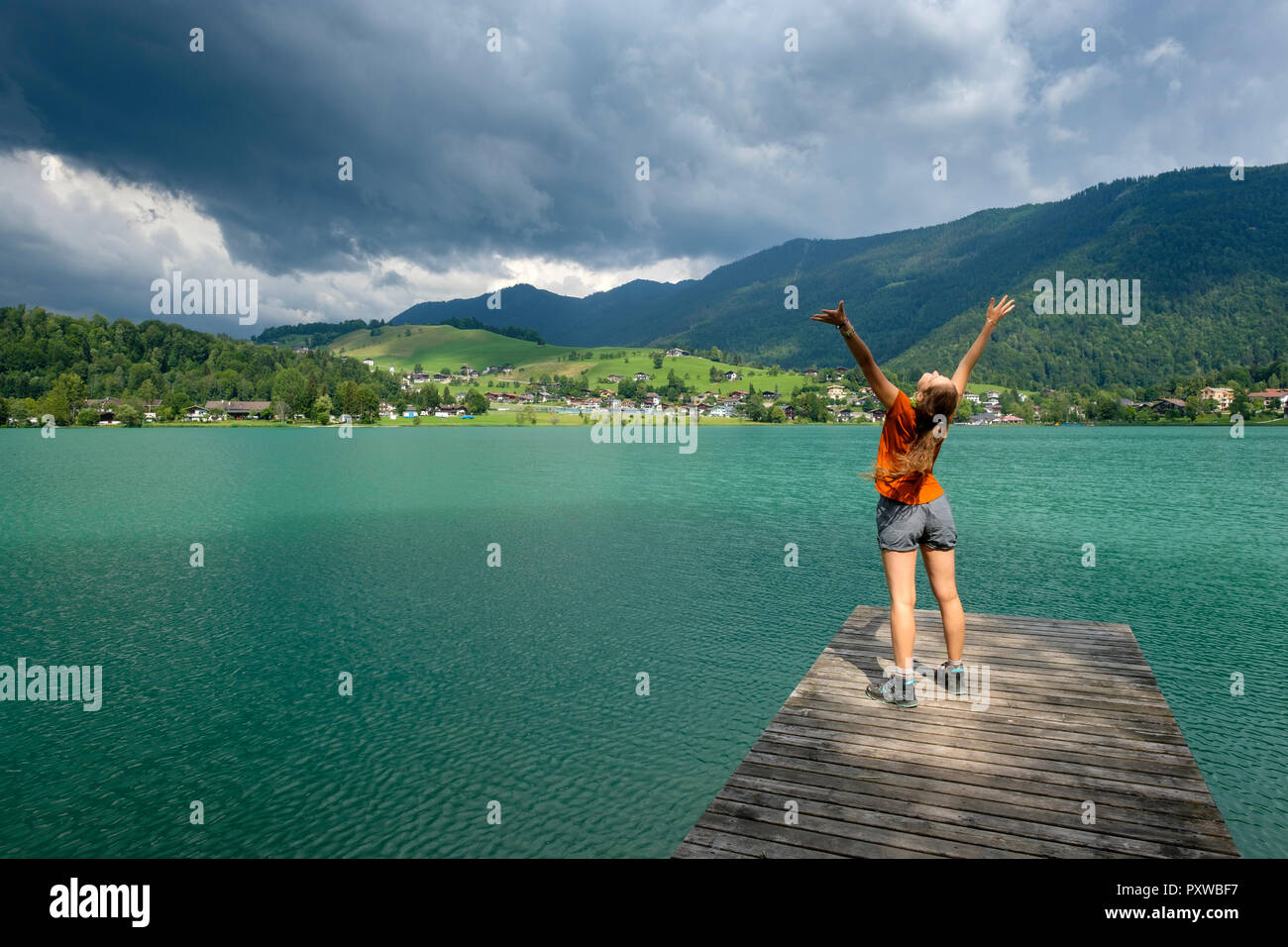 Teenager standing on wooden jetty, raised arms - Stock Image