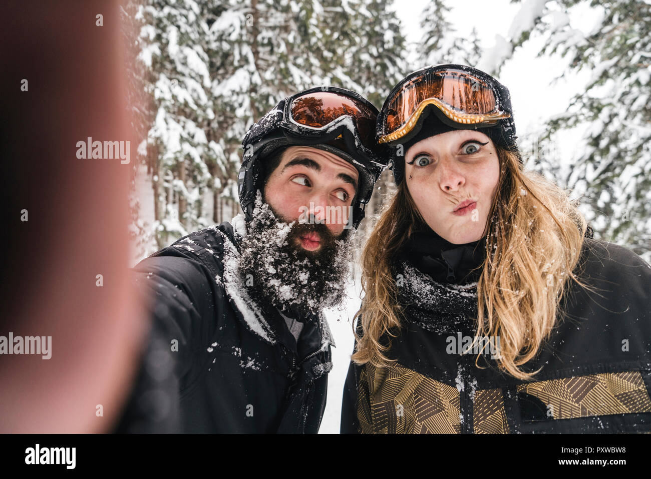 Selfie of happy couple in skiwear grimacing in winter forest - Stock Image