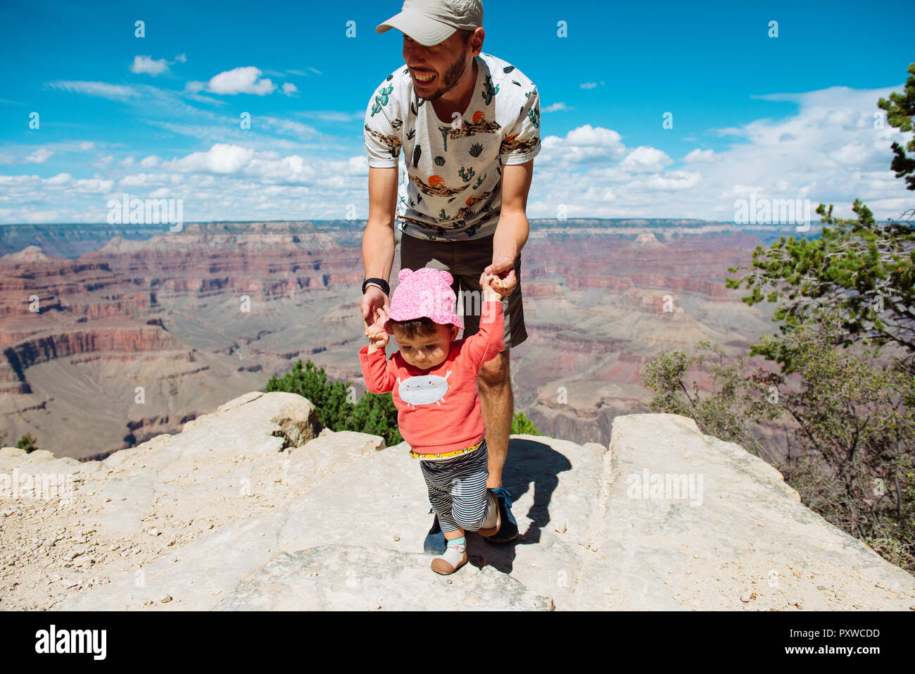 USA, Arizona, Grand Canyon National Park, father and baby girl  on viewpoint, girl learning to walk - Stock Image