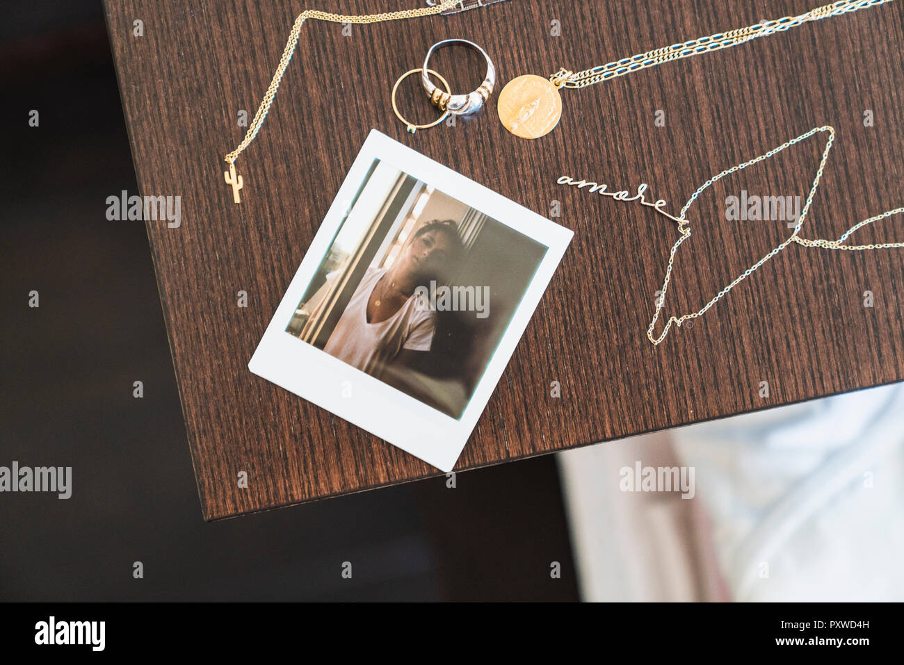 Instant photo of young woman next to jewelry on wooden table - Stock Image