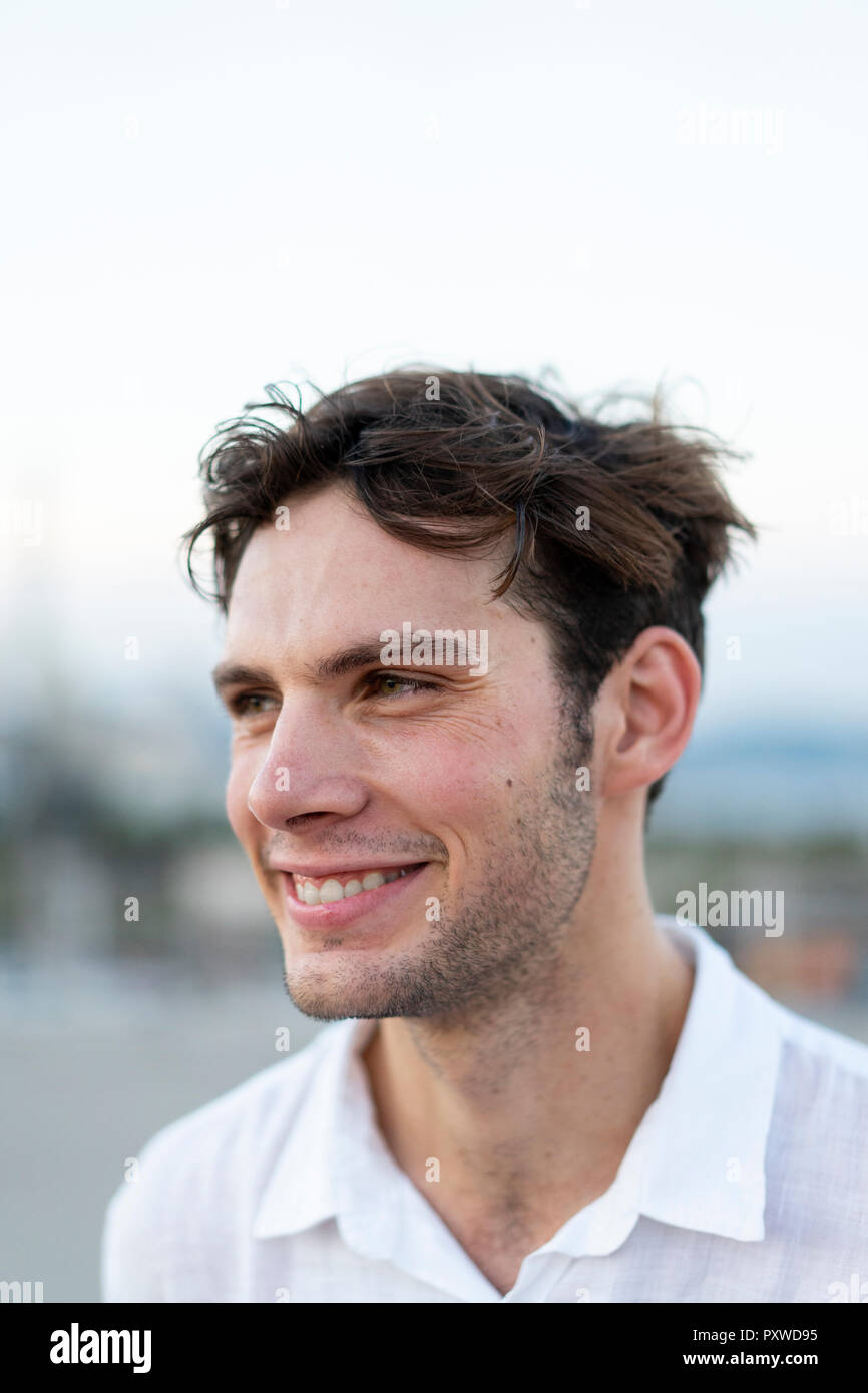 Portrait of smiling young man with tousled hair outdoors - Stock Image