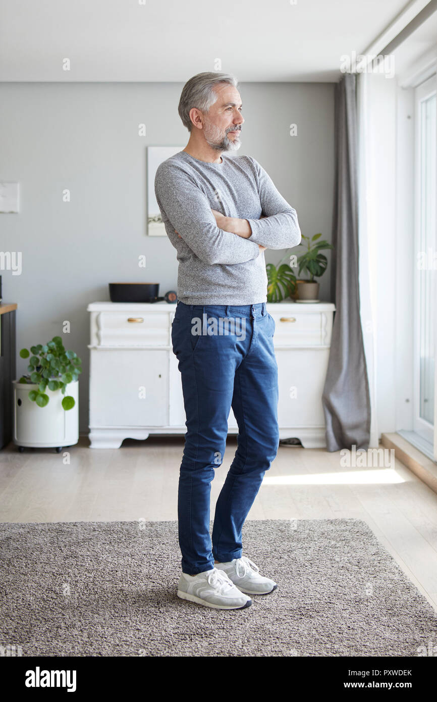 Mature man standing in his living room looking out of window - Stock Image