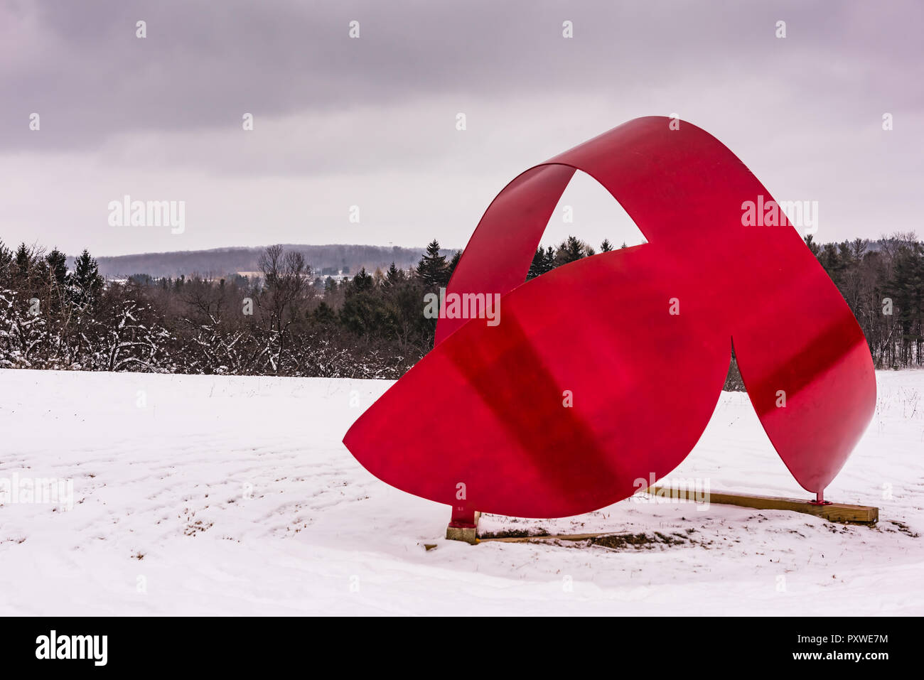 Whales Tail, a red aluminum sculpture by Miriam Nelson, punctuates winter landscape at the Stone Quarry Hill Art Park in the town of Cazenovia in Madi Stock Photo