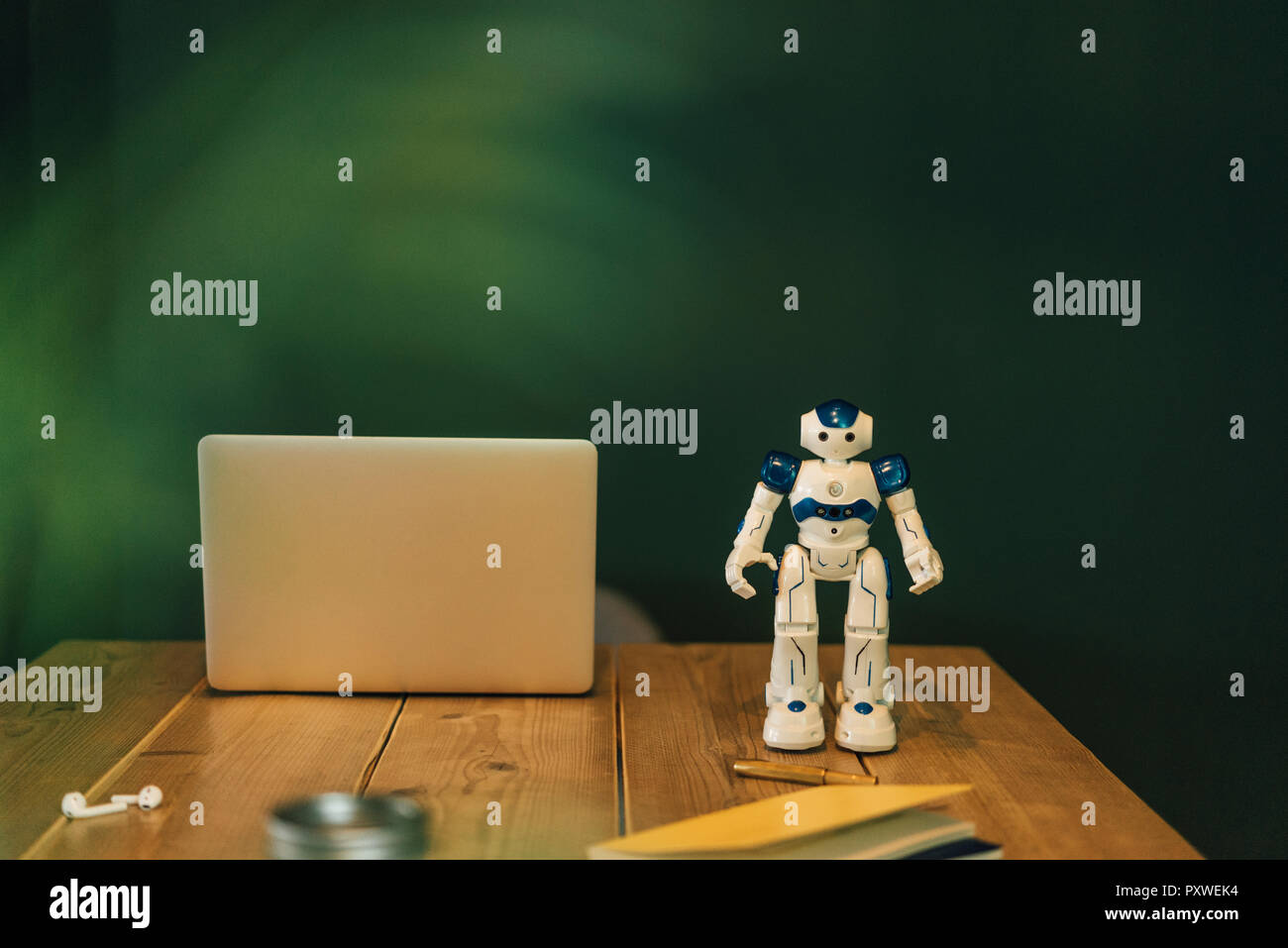 Toy robot and laptop on work table Stock Photo