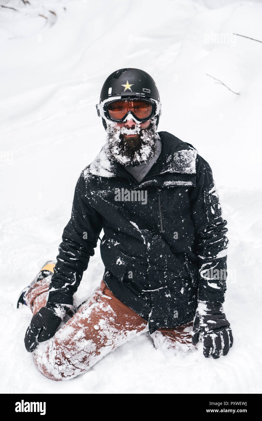 Snow-covered young man in skiwear kneeling in snow - Stock Image