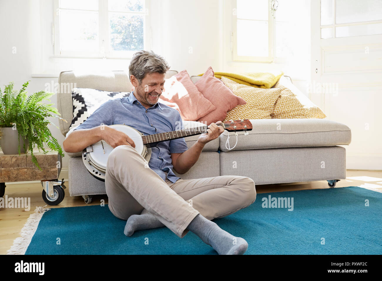 Man sitting on floor, playing the banjo - Stock Image