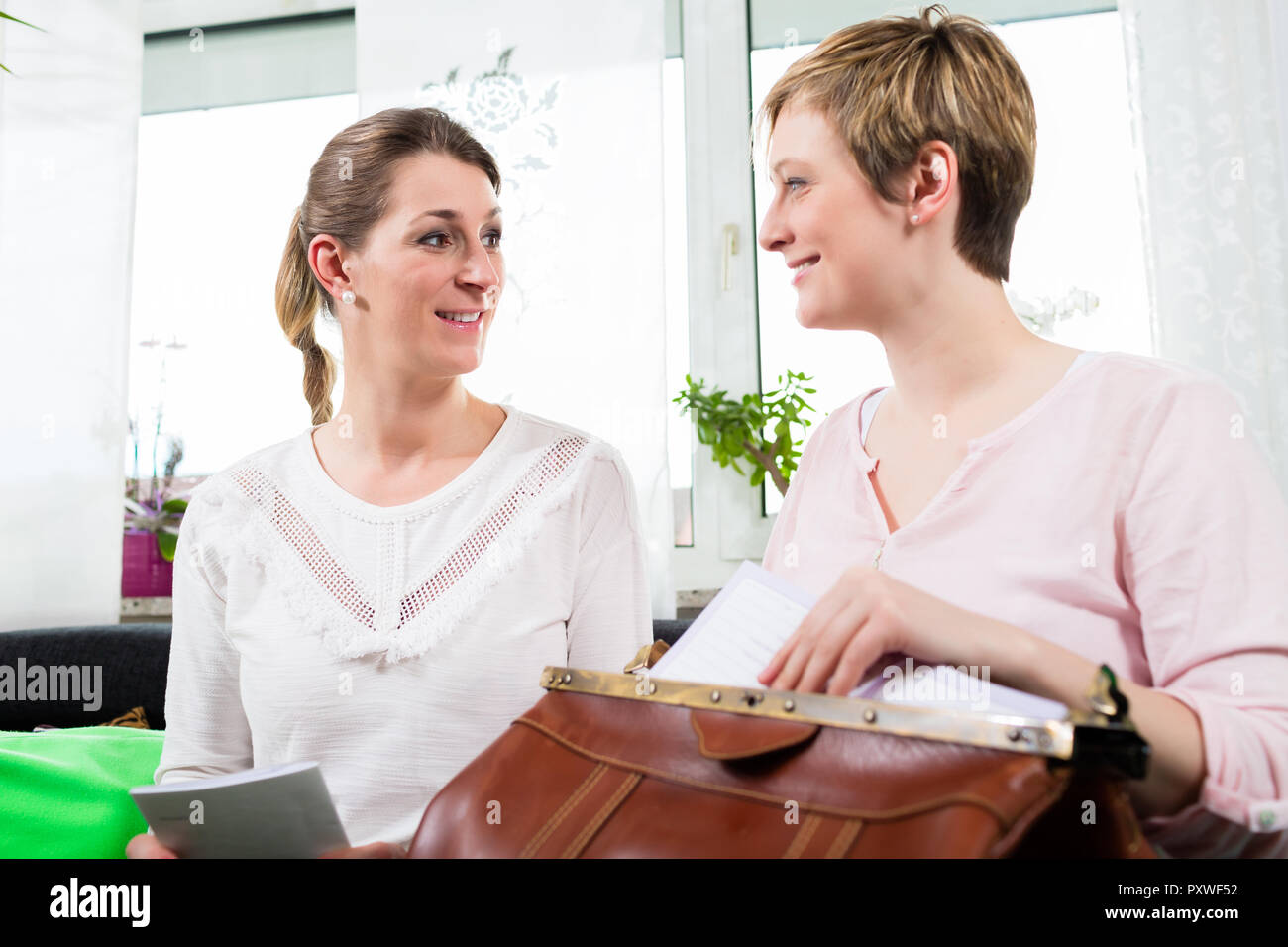Woman sitting with postnatal instructor - Stock Image