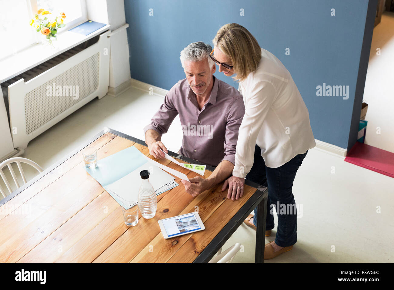 Mature couple with documents and tablet at home - Stock Image