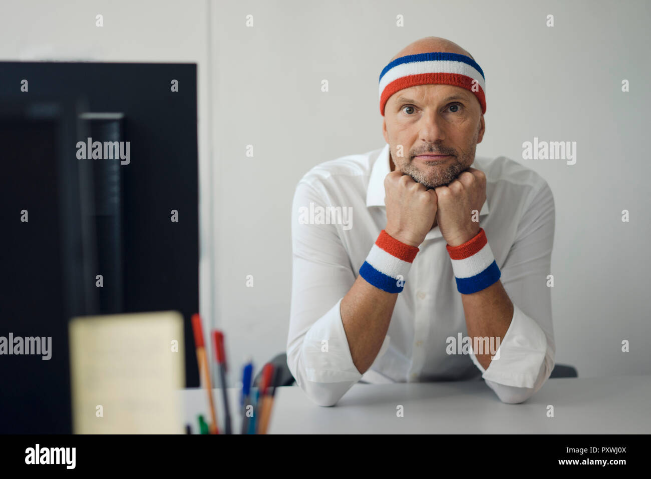 Businessman sitting in office, wearing sweat bands - Stock Image