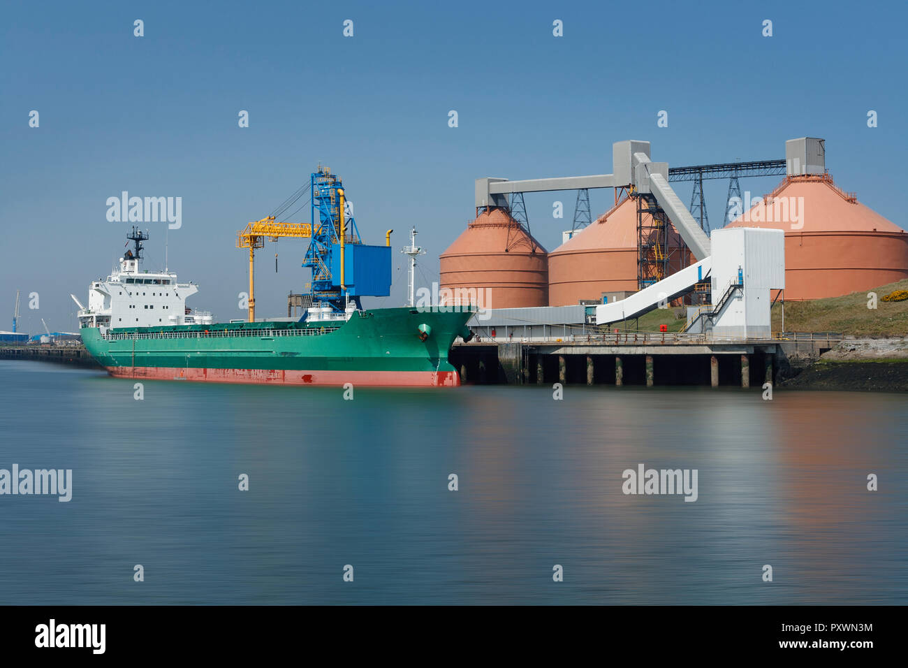 Unloading of a cargo ship in an industrial port, on a summers day with blue skies, and silos in background. - Stock Image