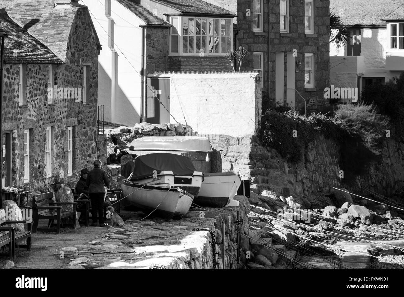 Black and White image of a small part of Mousehole harbour, beached boats and traditional fishermen's cottages with people chatting. - Stock Image