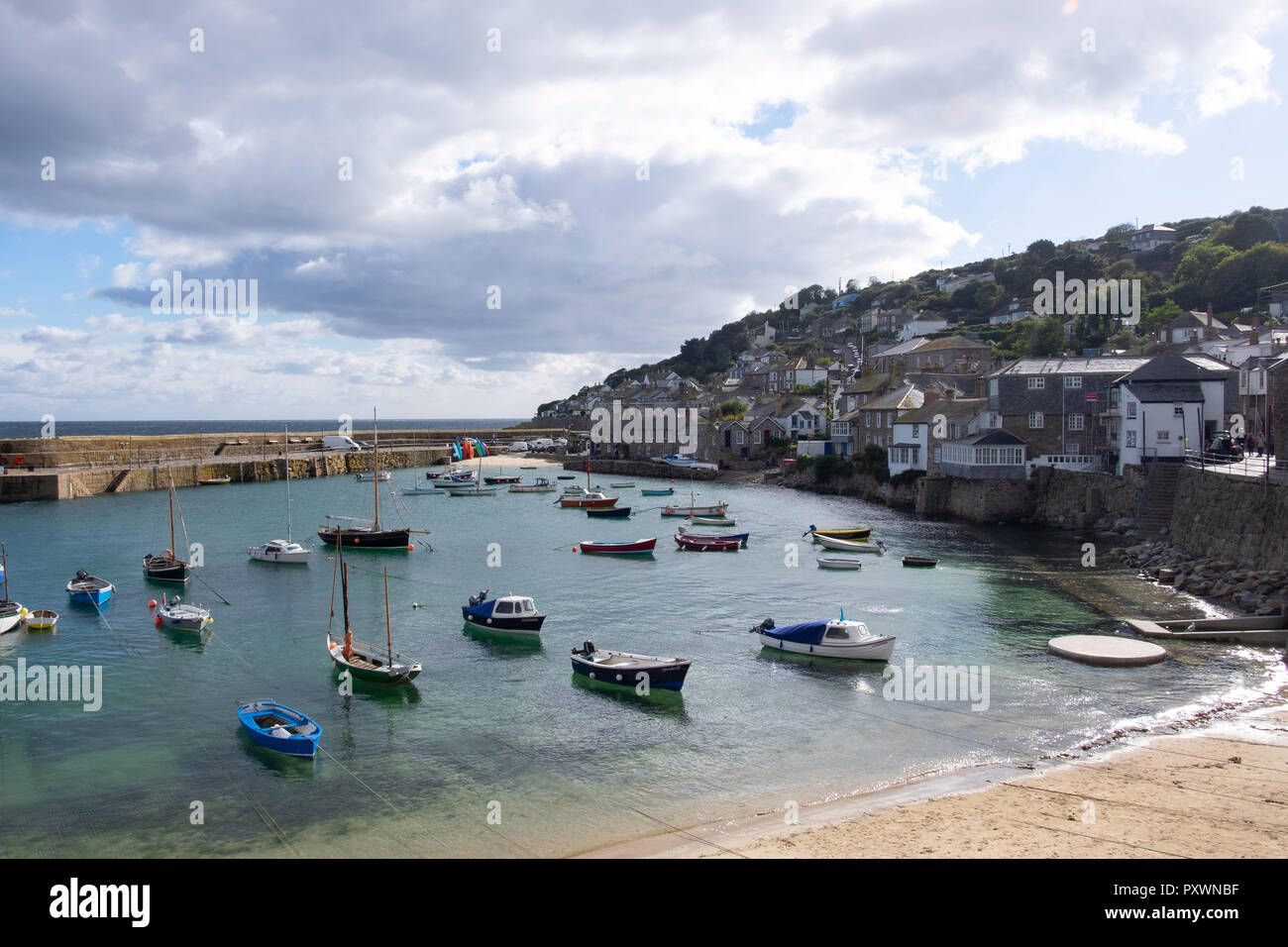 Wide angled view of Mousehole harbour in Cornwall showing the water in at high tide with many little bobbing boats. - Stock Image