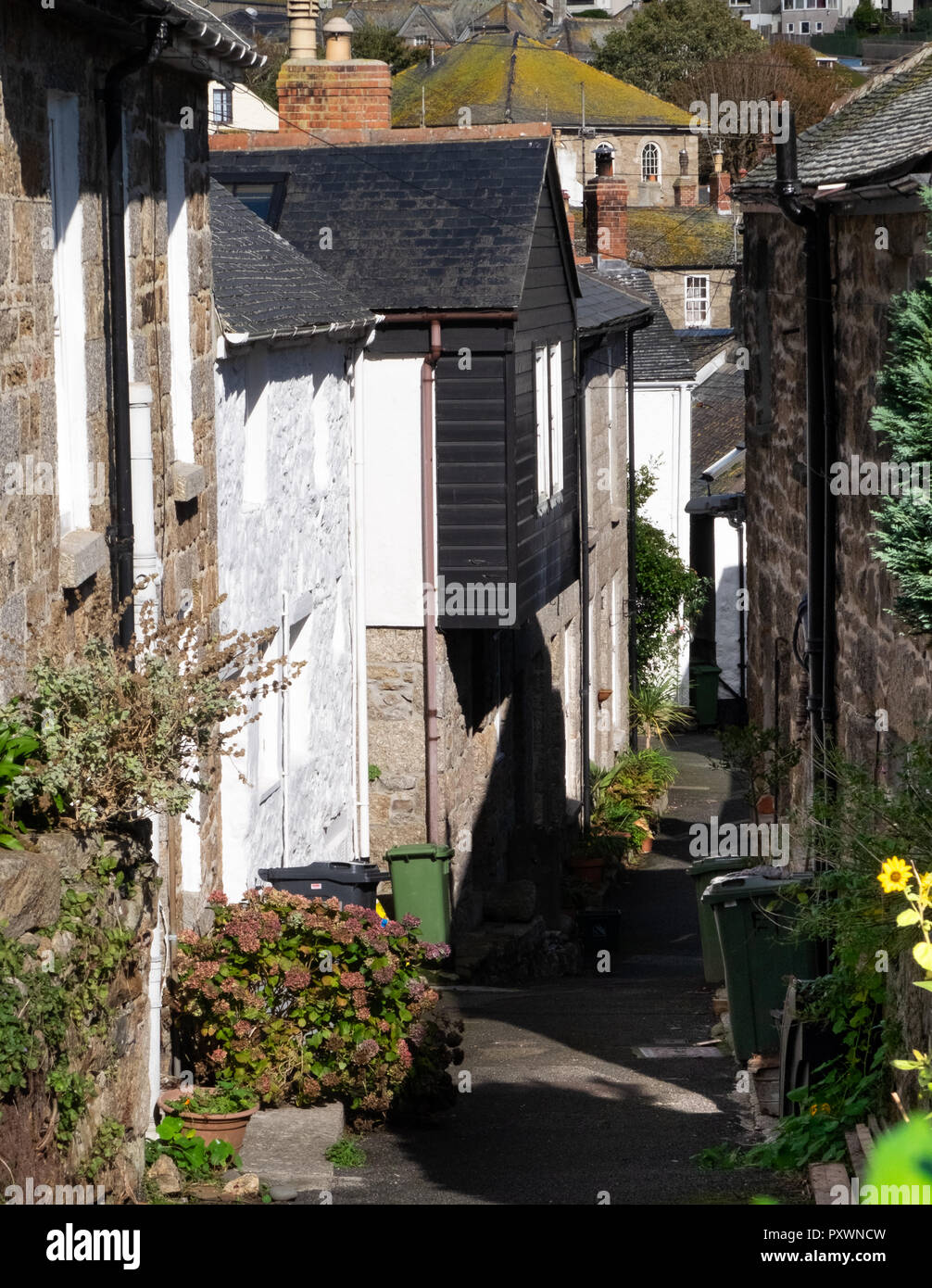 View from above of a very narrow street of terraced traditional village cottages in Mousehole, Cornwall. Green dustbins have to be out on the street. - Stock Image