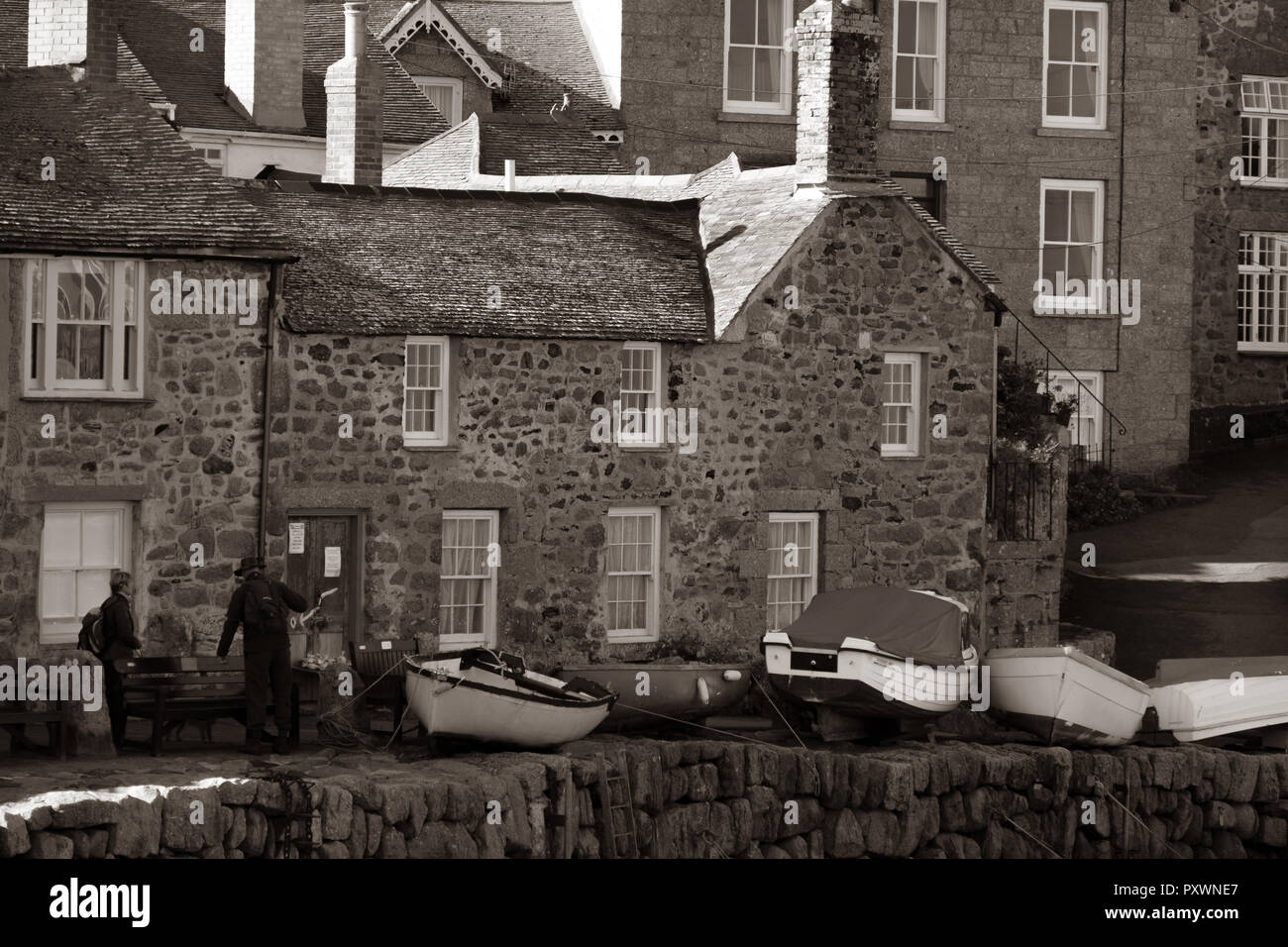Sepia toned close up of period fishing cottages, people and boats pulled out of the water on the quayside at Mousehole, Cornwall. - Stock Image