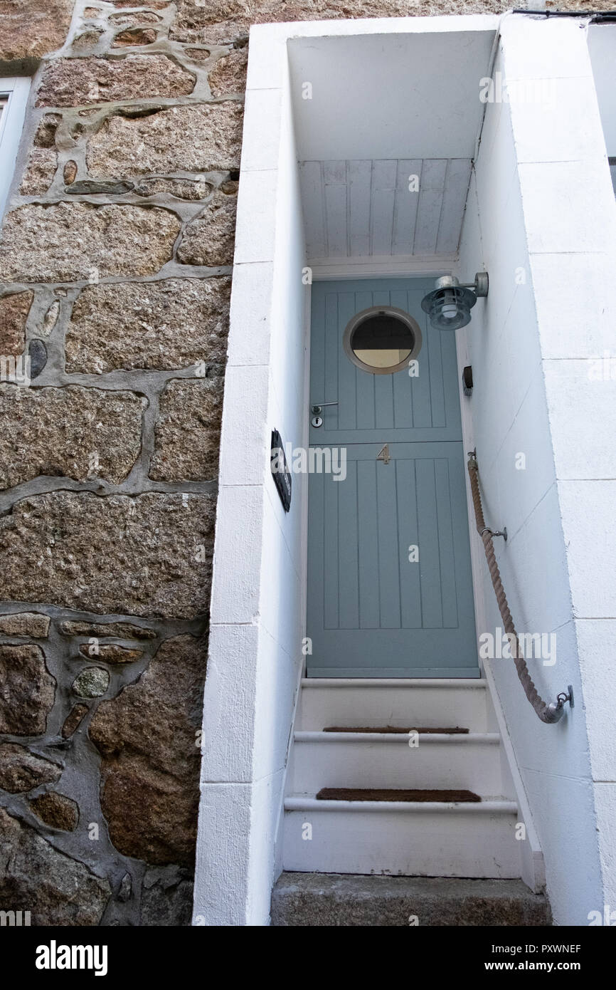 Period style wooden doorway with steep steps off a narrow alleyway in Mousehole Cornwall - Stock Image