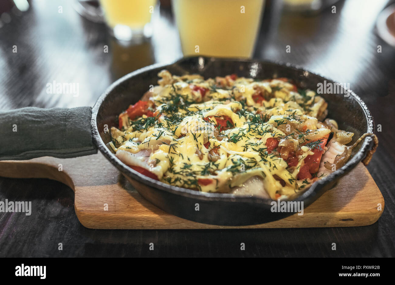 Frying pan with meat, vegetables and potatoes under melted cheese with golden beer Stock Photo