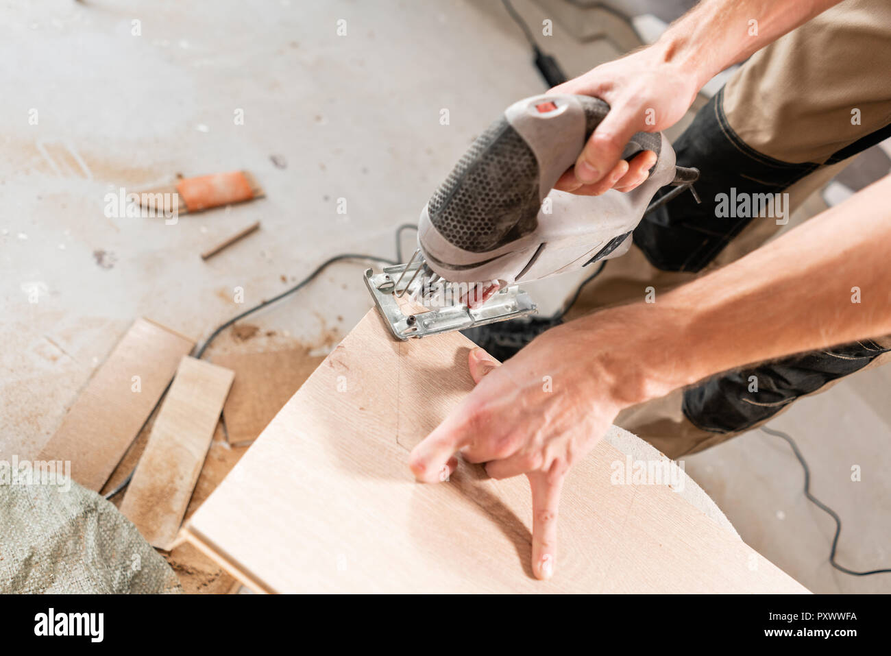 Male worker cuts the laminate Board with an electrofret saw. installing new wooden laminate flooring. concept of repair in house. - Stock Image