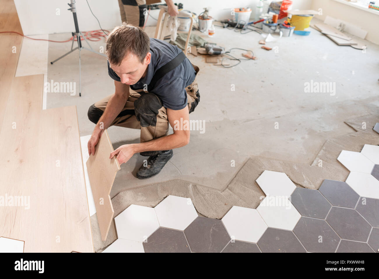 Male Worker Installing New Wooden Laminate Flooring The