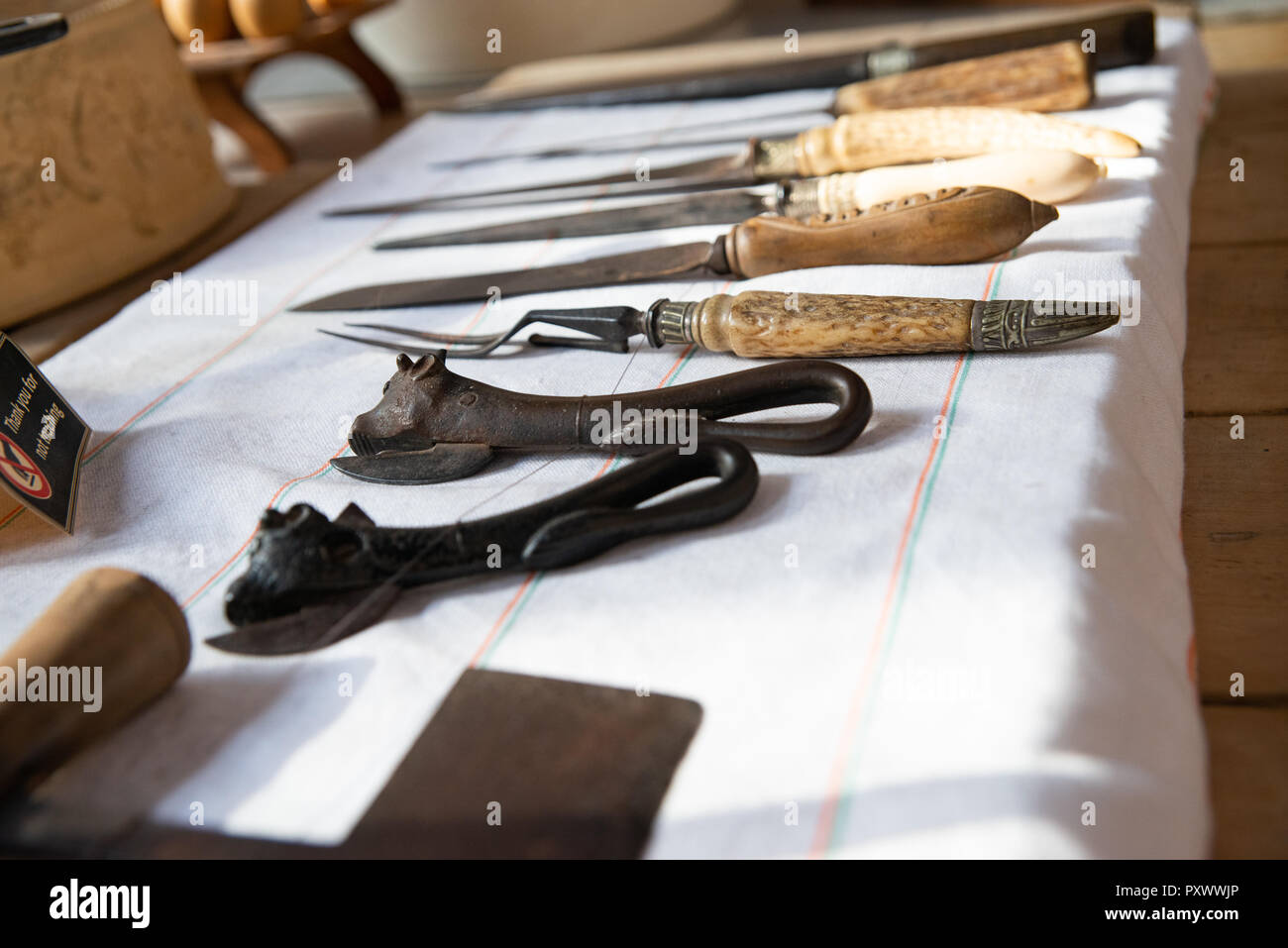 An array of Victorian or earlier kitchen utensils, openers, knives, forks and other equipment laid out neatly on a cloth at Lanhydrock, Cornwall - Stock Image