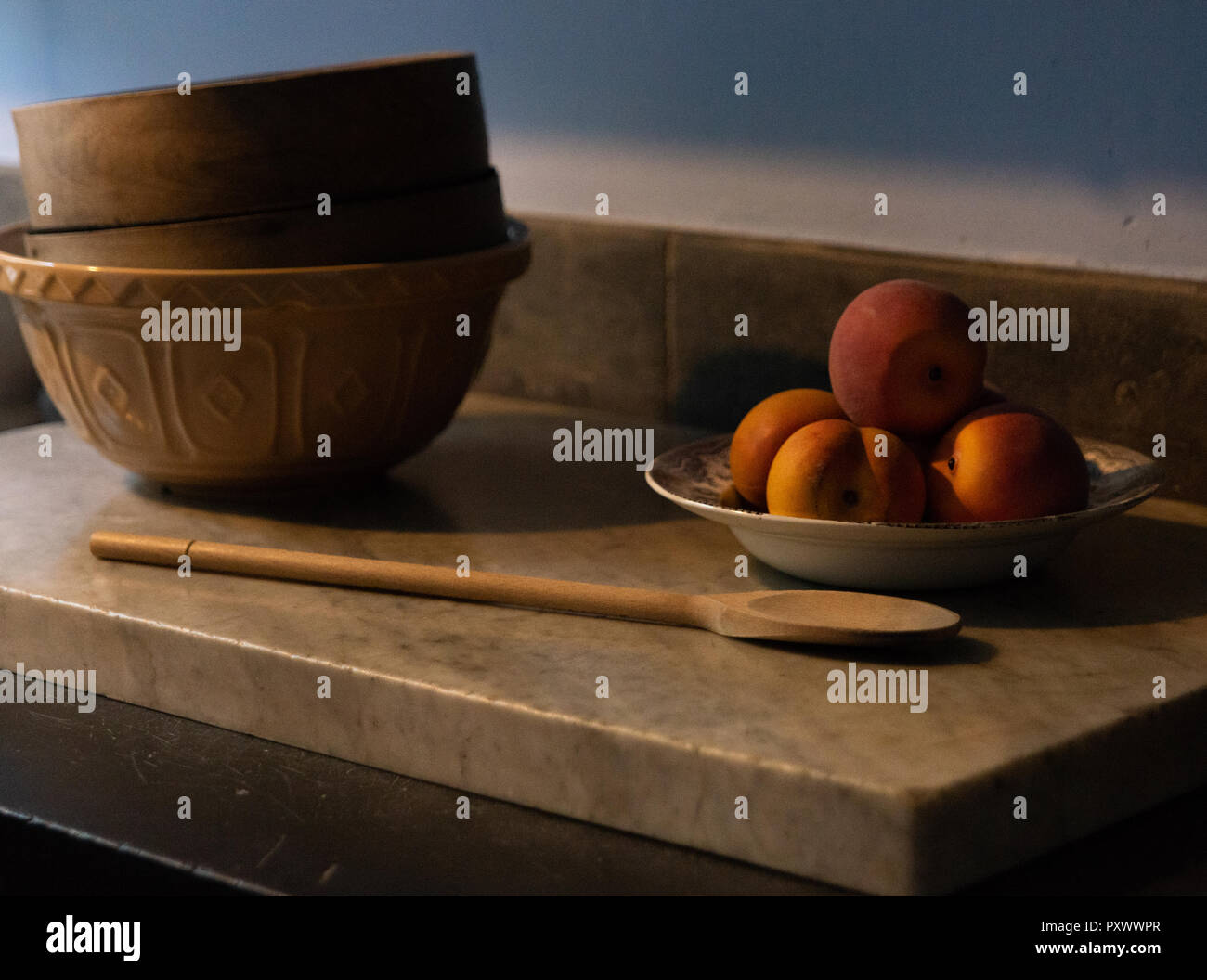 Arrangement of mock peaches in a round white bowl together with a small stack of mixing bowls and a wooden spoon on a marble work bench. - Stock Image