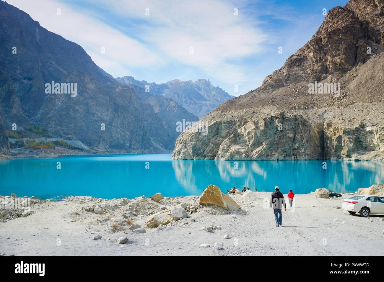 Men walking to ride a boat at the Attabad lake. Gojal, Hunza, Gilgit-Baltistan, Pakistan. - Stock Image