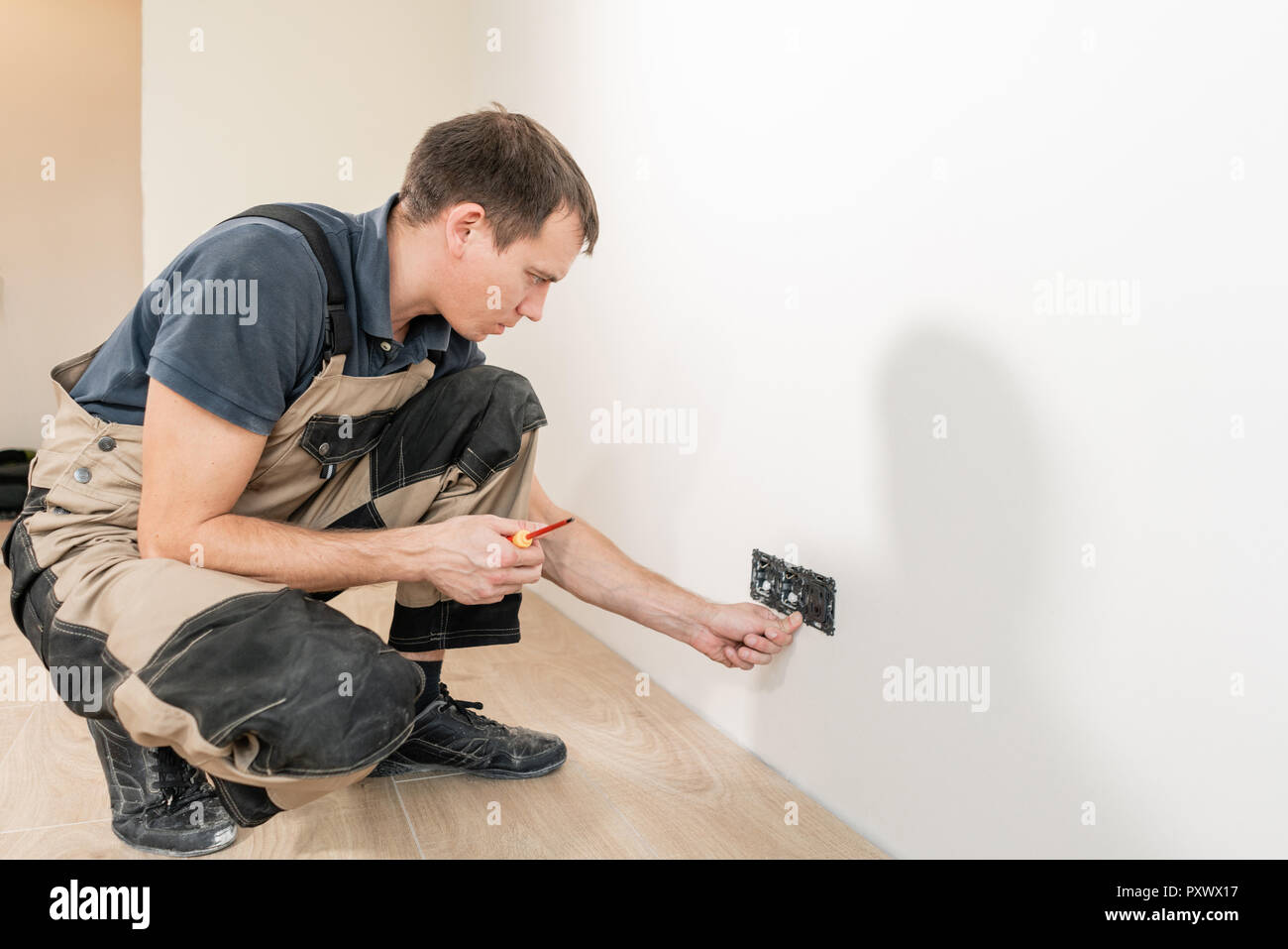 One Electrician Worker At Wiring Cable And Light Switch Or Power A With Wall Outlet Socket Installation Work