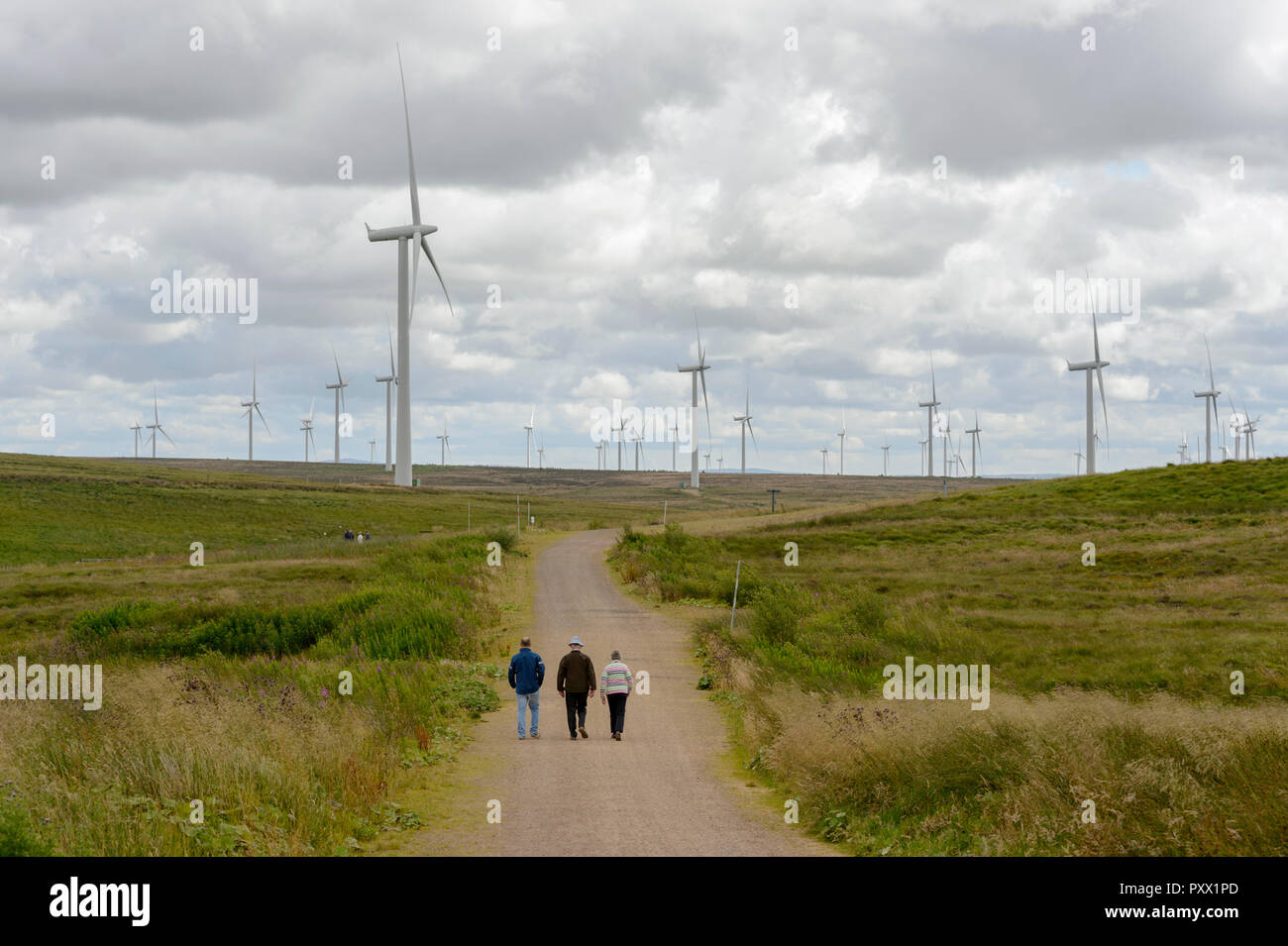 Visitors wander among the turbines at Whitlee Wind Farm. - Stock Image