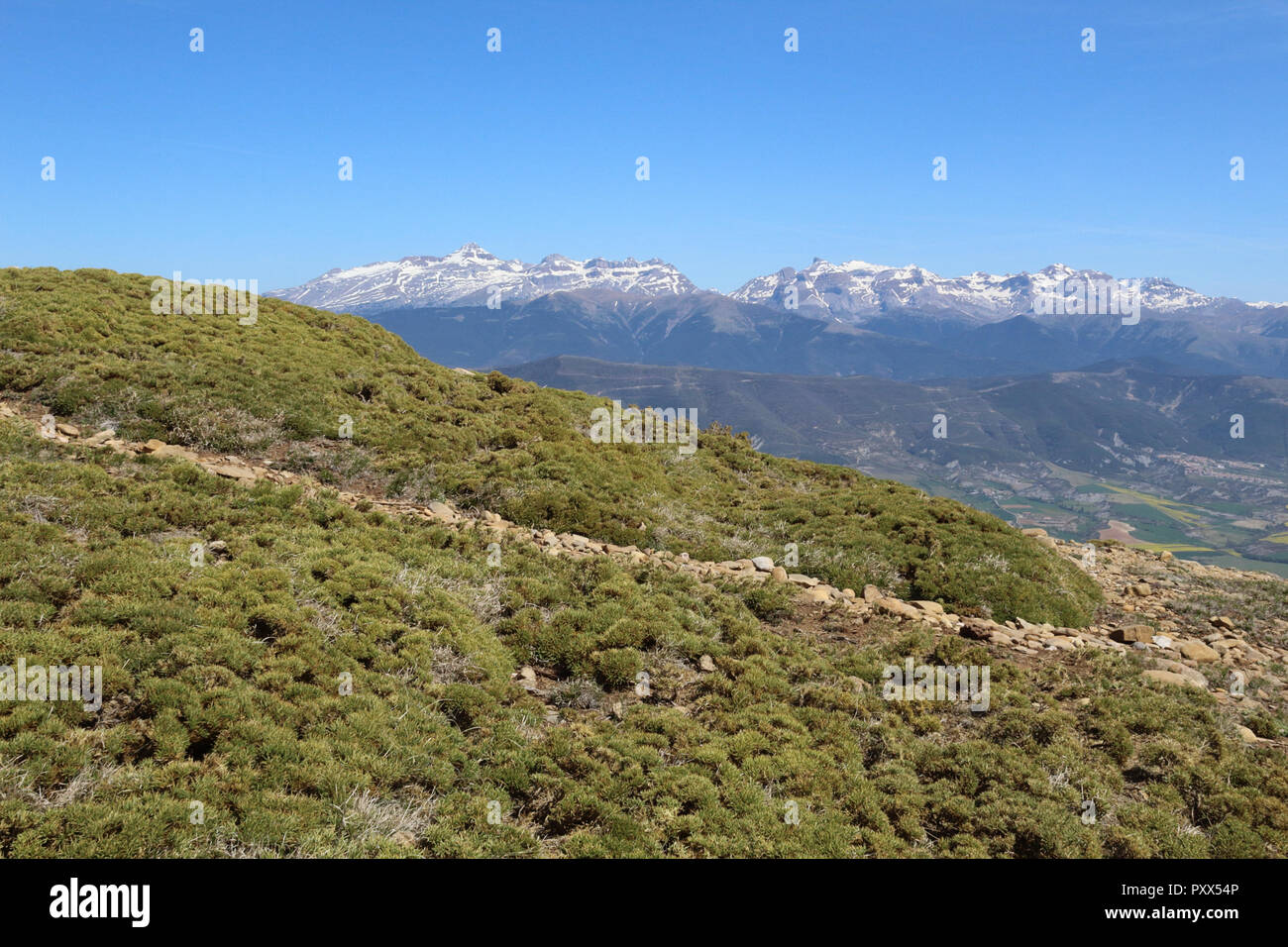A landscape of snow-clad Pyrenees mountains and a wide valley with blue cloudy sky and some bushes in Peña Oroel, Aragon region, Spain - Stock Image